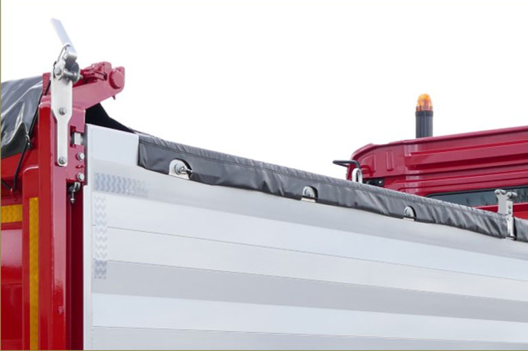 An eccentric bearing on the top border of the tipper body allows the retensioning of the side roll-up tarpaulin