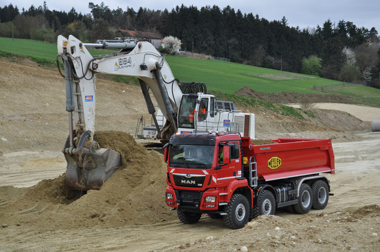 Rear tipper P436 in action with digger